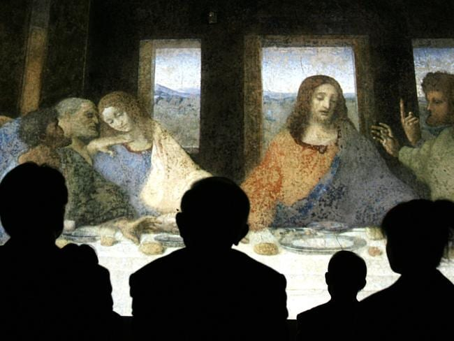 Guests look at a life-sized projected image of Leonardo da Vinci's The Last Supper. The Apocalypse of James details the purported advice and prophecies Jesus (in orange) gave his brother James (leaning left, with white cloak) before his death. Picture: AFP