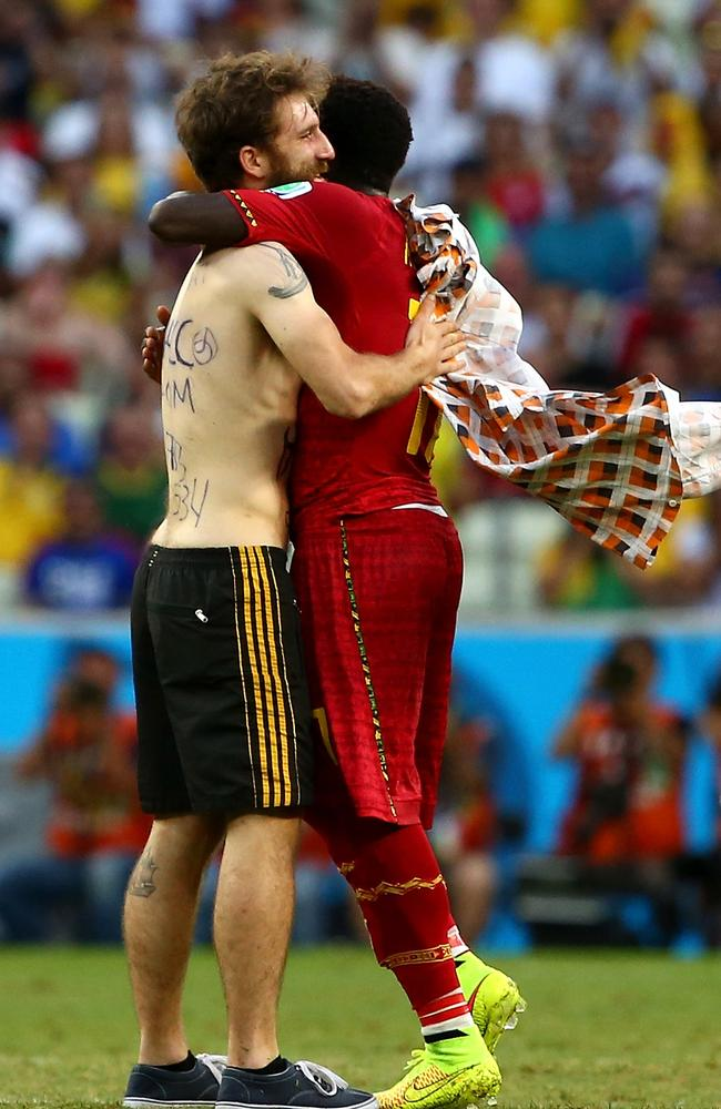 A pitch invader hugs Sulley Muntari of Ghana during the 2014 FIFA World Cup Brazil Group G match. There are claims he was a neo-Nazi from Poland.
