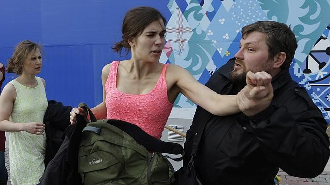 Attacked ... A russian security officer attacks Nadezhda Tolokonnikova and a photographer as she and fellow members of the punk group Pussy Riot, including Maria Alekhina, left, stage a protest performance in Sochi, Russia.