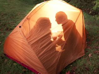 A couple camping enjoying wine and a kiss in their tent on the edge of the forest in autumn. Click to view similar images.