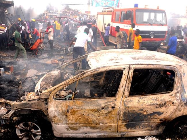 Absolute carnage ... firefighters and rescuers extinguish a fire at the scene of a bomb blast at Terminus market in the central city of Jos.