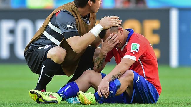 Chile's defender Gary Medel (R) is consoled after losing their match against Brazil.