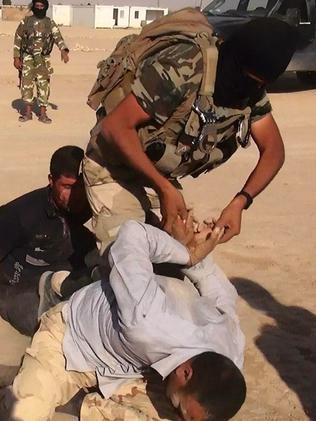Terror tactics ... A jihadist militant restraining an unidentified man at an undisclosed location inside Iraq.