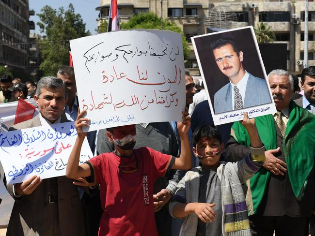 Syrians wave the national flag and wave portraits of President Bashar al-Assad as they gather in Aleppo's Saadallah al-Jabiri square to condemn the strikes.
