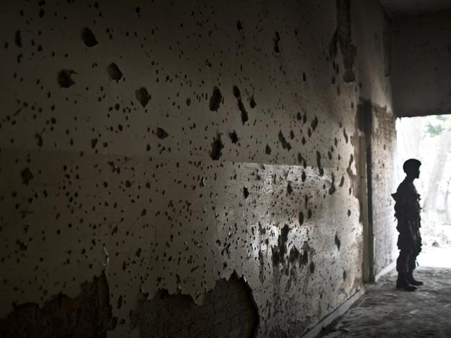 Aftermath ... a Pakistani army officer stands by a wall riddled with bullet marks inside the Army Public School attacked by Taliban gunmen, in Peshawar, Pakistan. Picture: AP