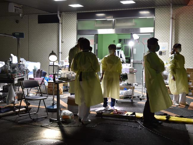Medical staff prepare to evacuate patients from the hospital in Kumamoto City over fears it could collapse as a wave of aftershocks shake the area.