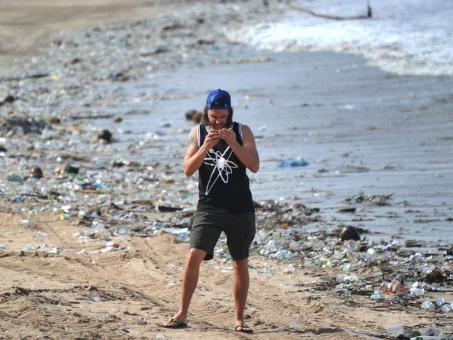A tourist stands between plastic rubbish at Kuta beach near Denpasar, on Indonesia's tourist island of Bali on December 19, 2017. The palm-fringed shoreline of Bali's Kuta beach has long been a favourite with tourists seeking sun and surf, but nowadays its golden shores are being lost under a mountain of garbage. / AFP PHOTO / SONNY TUMBELAKA / TO GO WITH Indonesia-rubbish-Bali-environment,FEATURE by Bagus Saragih