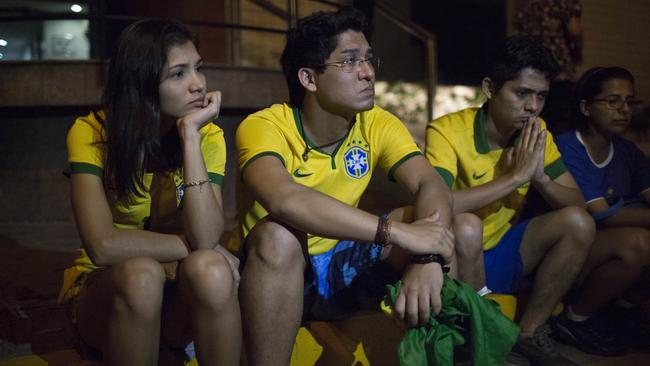 Anxious Brazil soccer fans sit outside the Sao Carlos hospital.