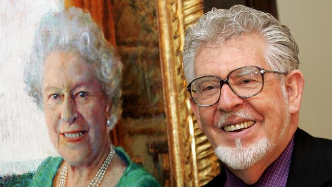 Rolf Harris with his portrait of the Queen. Buckingham Palace won't confirm the painting's whereabouts as the entertainer faces court on child-sex charges. Picture: hris Jackson/Getty Images