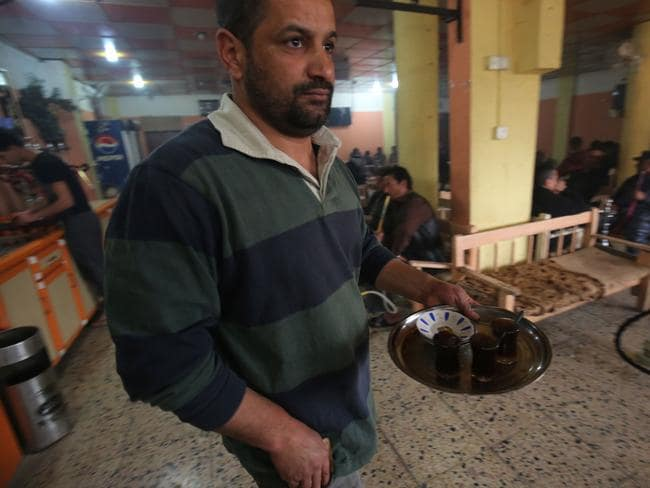 An Iraqi man serves tea at a cafe in the Hamam al-Alil area, south of Mosul this month. Picture: Ahmad al-Rubaye