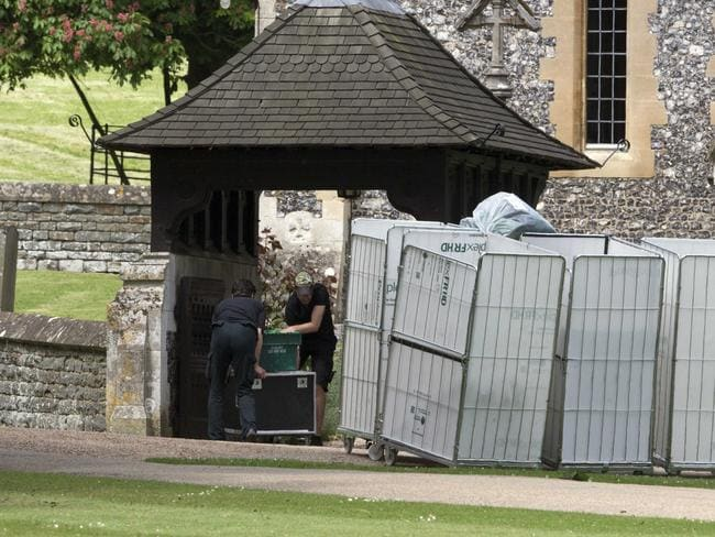 Staff deliver more equipment to the 12th century church. Picture: Splash News