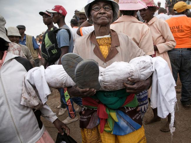 Isabel Malala Razafindrakoto carries the wrapped body of her son, who died aged just three years old. Picture: AFP/RIJASOLO