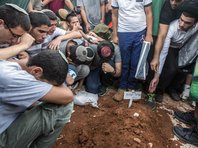 Burial ... elatives and friends gather around a grave, as Gilad Shaer, 16, Naftali Frenkel, 16, and Eyal Ifrach, 19, are buried side-by-side in the central Israeli town of Modiin.