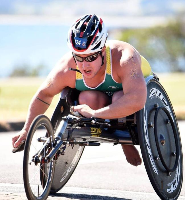 Scott Crowley competing in a para- triathalon - he is in a speed wheelchair with a helmet on and a third wheel in front.