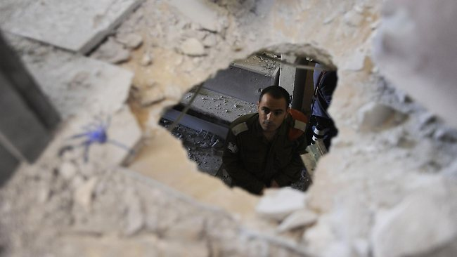 An Israeli soldier inspects the damage caused to a building by a rocket launched by Palestinian militants from Gaza strip hitting the city of Ashkelon. Picture: AFP