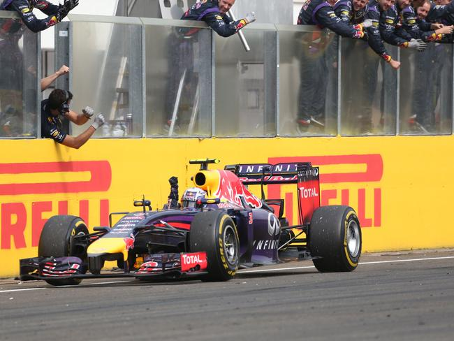 Daniel Ricciardo drives past the Red Bull crew members to celebrate his Hungarian GP win with them.