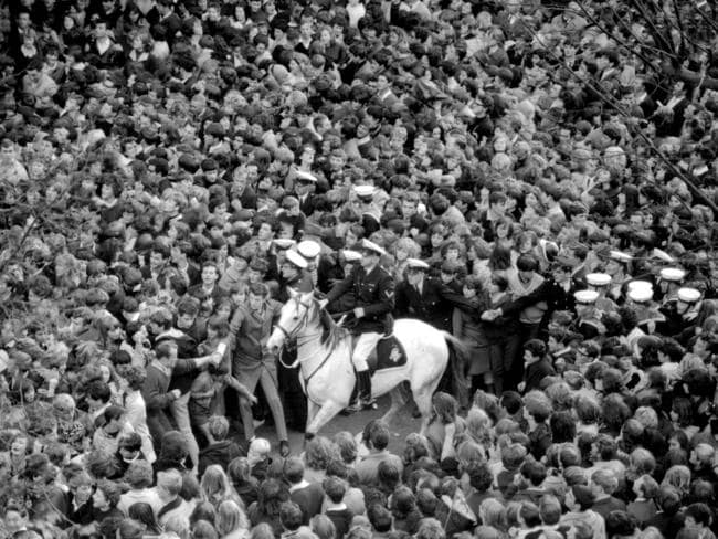 June 14, 1964: Mounted policeman face a hopeless task trying to control 10,000 people who flooded Exhibition Street to catch a glimpse of The Beatles at the Southern Cross Hotel. Picture: Herald Sun Image Library.