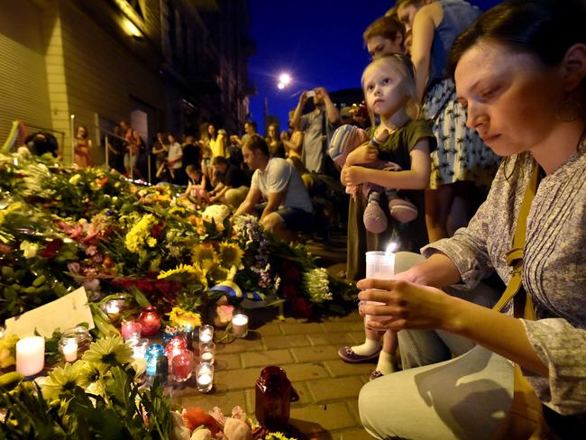 United in grief ... woman lights a candle in front of the Embassy of the Netherlands in Kiev following the crash. Picture: Sergei Supinsky