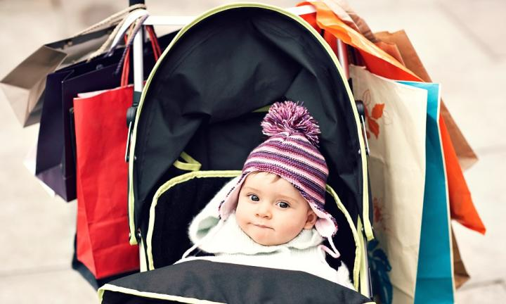 Portrait of cute baby in stroller hung with shopping bags