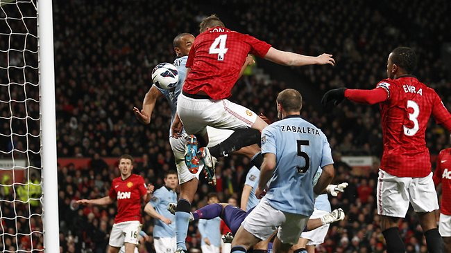 Manchester United's Phil Jones, centre, heads the ball which hit Vincent Kompany, left, of Manchester City to score an own goal at Old Trafford. Picture: Jon Super
