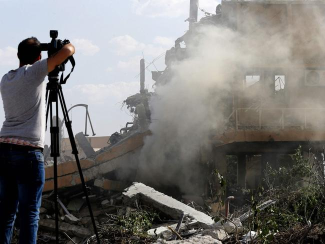 A journalist films the wreckage of a building described as part of the Scientific Studies and Research Centre (SSRC) compound in the Barzeh district, north of Damascus, after the missile strike. Picture: AFP Photo/Louai Beshara