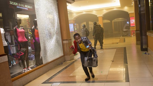 A woman who had been hiding during the gun battle runs for cover after armed police, seen behind, enter the Westgate Mall in Nairobi, Kenya.