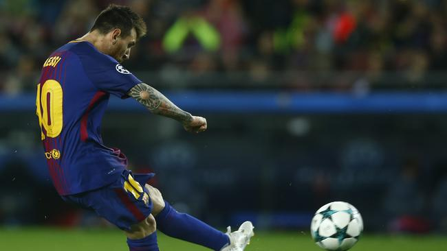 Barcelona's Lionel Messi kicks the ball to score