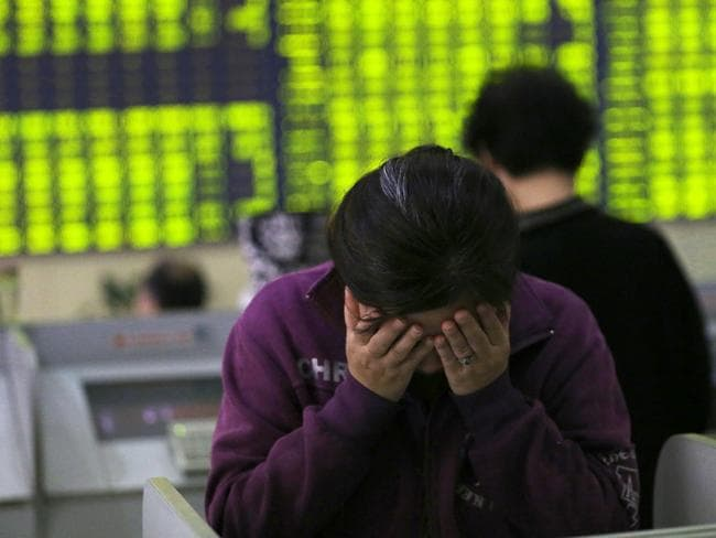 A woman rubs her face as she stands in a stock brokerage house in Nantong.