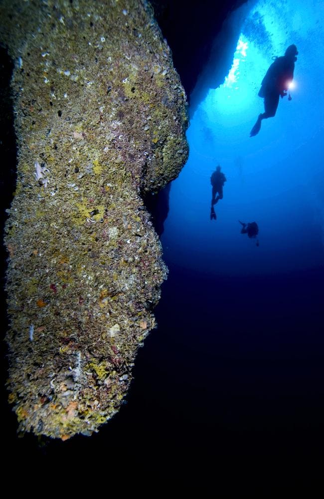 Divers descend to stalactites in Blue Hole. Tim Rock/Lonely Planet