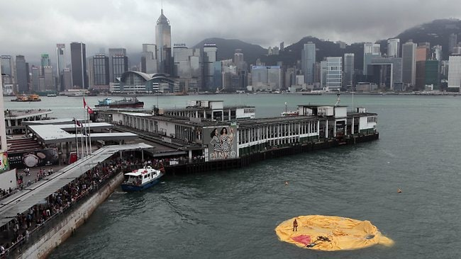 A workman (R) stands on the remains of a 16.5-metre-tall inflatable rubber duck art installation as it lies deflated in Hong Kong's Victoria Harbour.