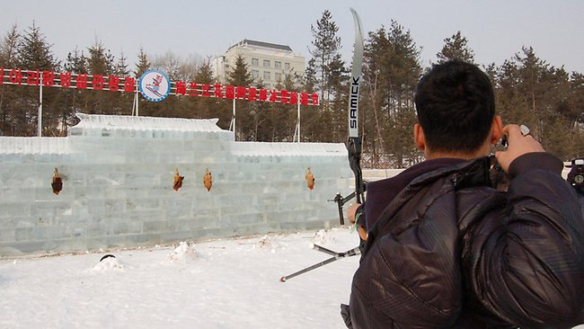 A tourist prepares to shoot roosters at the Ice Festival. Picture: QQ