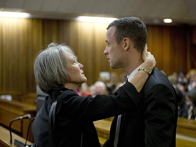 Apology ... South African Paralympic track star Oscar Pistorius speaks with a family member during his murder trial. Picture: AFP
