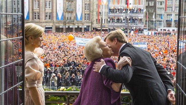 Princess Beatrix of the Netherlands kisses her son King Willem-Alexander of the Netherlands as HM Queen Maxima of the Netherlands looks on during a short address on the balcony of the Royal Palace to greet the public after the abdication of Queen Beatrix . (Photo by RVD/Jeroen Van Der Meyde/Getty Images)