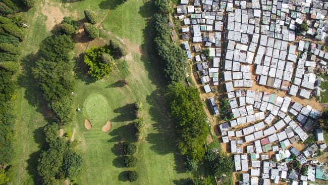 "Miller says of this photo: ""Papwa Sewgolum Golf Course is located along the lush green slopes of the Umgeni River in Durban. Almost unbelievably, a sprawling informal settlement exists just meters from the tee for the six hole."" Picture: Johnny Miller/Millefoto/Rex Shutterstock"