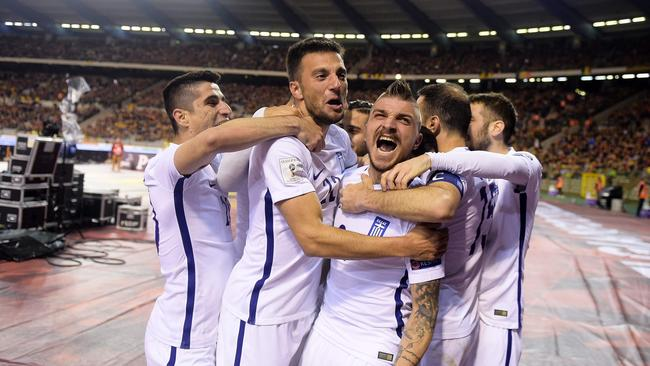 Greece's players celebrate after scoring.