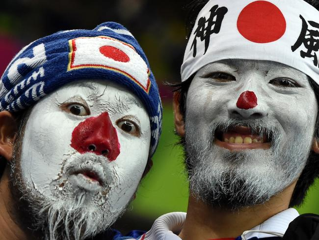 Japanese fans with their faces painted in the colours of their national flag await the kick-off of a Group C football match between Ivory Coast and Japan.