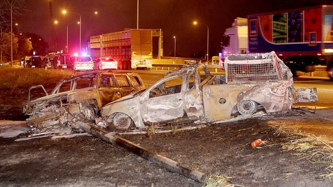 The burnt-out shells of the two vehicles on the side of the Gateway Motorway last night. Pic: Marc Robertson