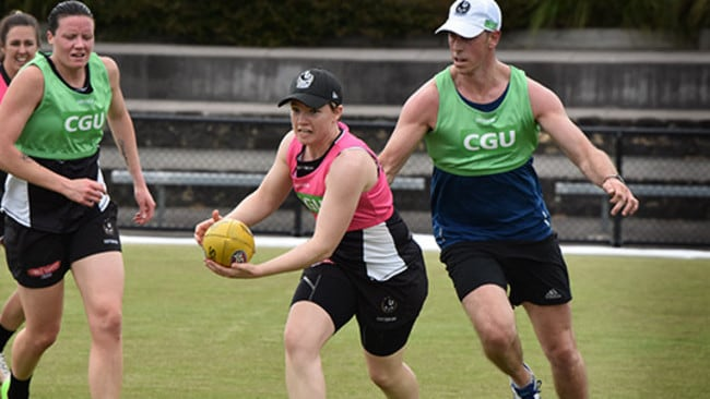 Jess Duffin trains during Collingwood's AFLW training camp as a familiar face gives chase, premiership captain Nick Maxwell. Picture: Collingwood FC