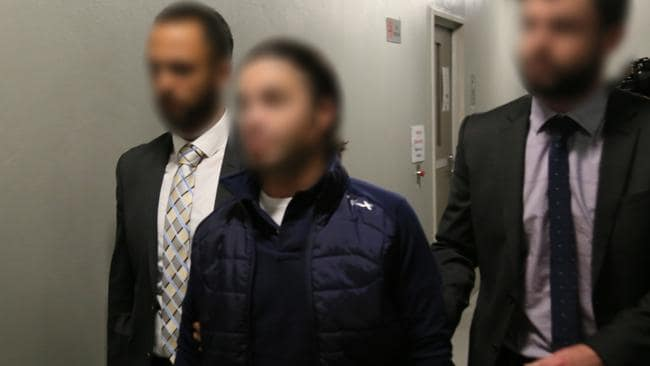 AFP officers escort the four men, arrested as part of Operation Veyda, into Sydney Police Centre on Sunday night. Picture: Australian Federal Police