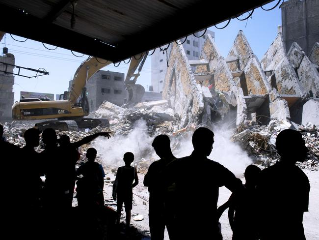 Truce ... adults and children watch as the rubble left from a collapsed building that was targeted by Israeli air strikes overnight is cleared off a street in Gaza City on August 26, 2014. Picture: Roberto Schmidt