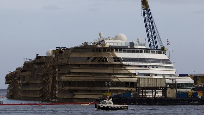 Costa Concordia's starboard side, which was submerged for 20 months, is coated in brown scum and algae, whereas its port side, which had remained out of the water, is still pristine white. (AP Photo/Andrew Medichini)