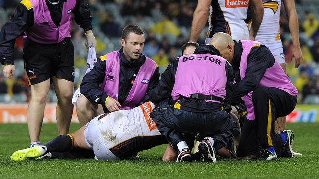 Eagle Dean Cox in the hands of the trainers after knock to the head. Picture: Daniel Wilkins