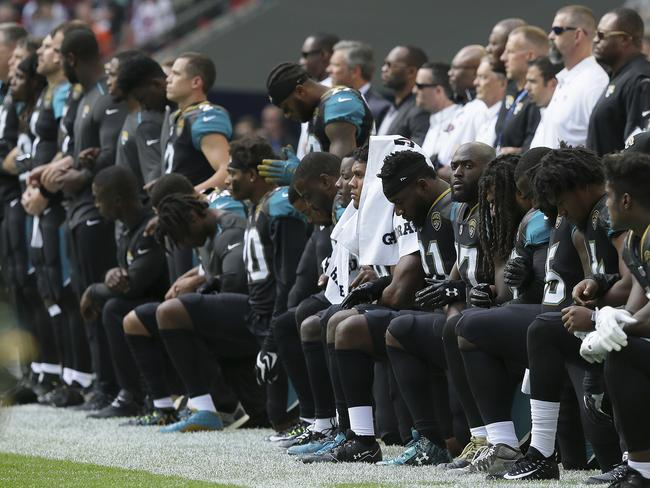 Jacksonville Jaguars players kneel down during the national anthem.