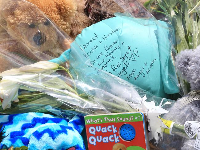 Tributes left at the wharf where Damien Little drove his sons to their deaths.