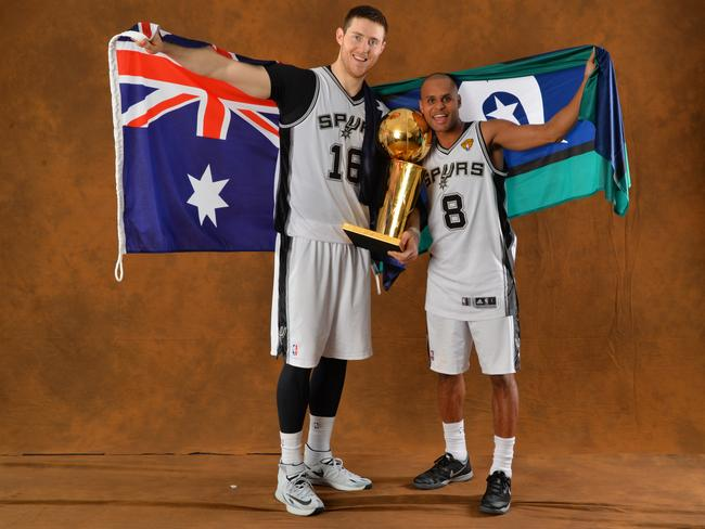 Aron Baynes and Patty Mills of the San Antonio Spurs poses for a portrait with the Larry O'Brien Trophy after defeating the Miami Heat in Game Five of the 2014 NBA Finals.
