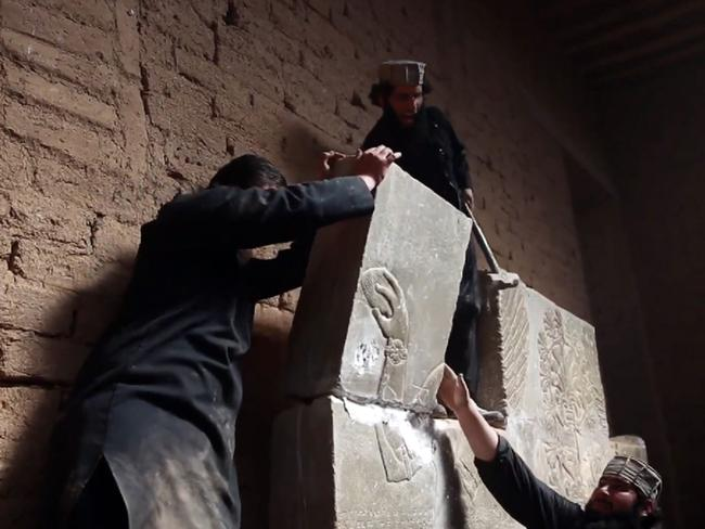 Members of the Islamic State (IS) militant group destroy a stoneslab with a sledgehammer at what they said was the ancient Assyrian city of Nimrud in northern Iraq.