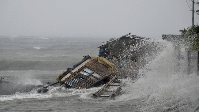 A house is engulfed by the storm surge brought about by powerful typhoon Haiyan that hit Legazpi city, Albay province in the Philippines. Picture: AP Photo/Nelson Salting