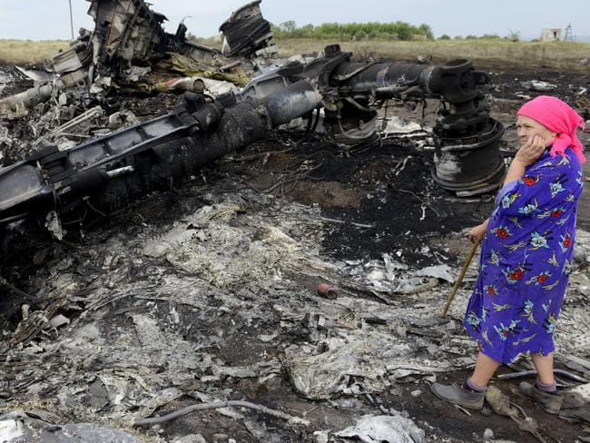 Final resting place ... A local woman stands among the wreckage at the site of the crash in Grabove. Picture: Alexander Khudoteply