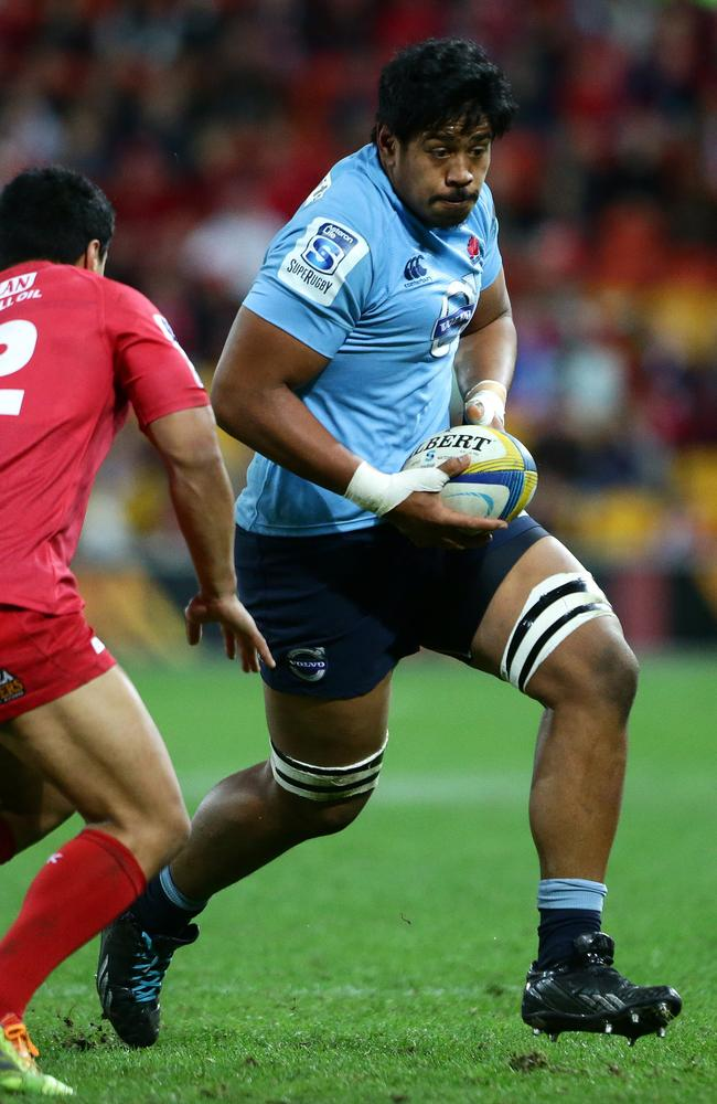 Giant Waratahs lock Will Skelton takes on the Reds defence.