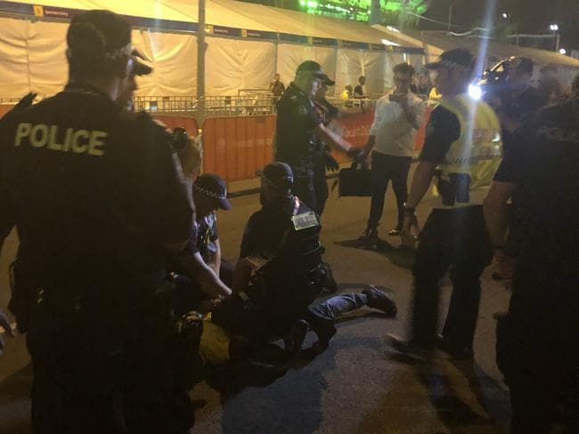 Aboriginal protesters are arrested by police during the Commonwealth Games opening ceremony. Picture: Britt Ramsey